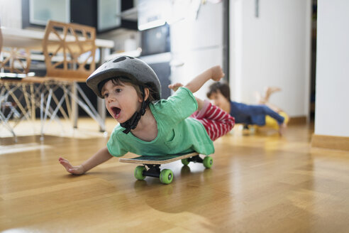 Toddler boy at home lying on skateboard wearing helmet having fun - AZOF00023