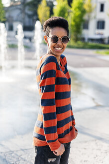 Portrait of happy young woman wearing sunglasses and striped pullover - GIOF04339