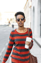 Portrait of young woman with coffee to go wearing sunglasses and striped pullover - GIOF04342