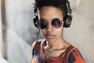 Portrait of young woman wearing sunglasses listening music with headphones - GIOF04345