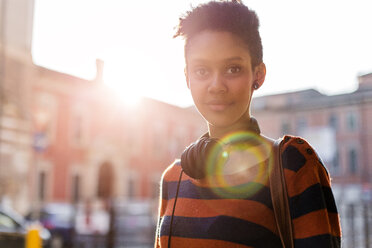 Portrait of smiling young woman with headphones at backlight - GIOF04348