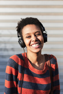 Portrait of laughing young woman listening music with headphones - GIOF04351
