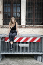 Portrait of smiling teenage girl sitting on barriers in the city - GIOF04372