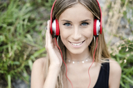 Portrait of smiling teenage girl wearing headphones - GIOF04378