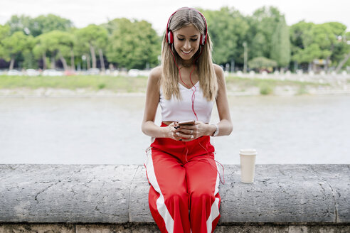 Smiling teenage girl wearing headphones and using cell phone at the riverside - GIOF04390