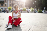 Smiling teenage girl with takeaway drink sitting on city square at sunset - GIOF04402