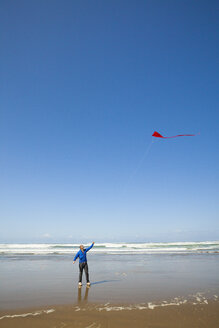 A young man looks up at his red kite in the sky while visiting a beach along the Oregon Coast - AURF04211