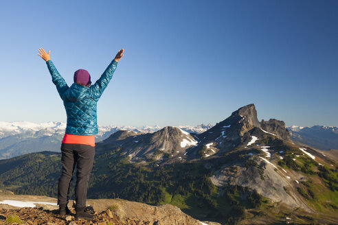 A young woman celebrates after reaching the summit of Panorama Ridge in Garibaldi Provincial Park, British Columbia, Canada. - AURF04217
