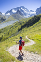 A colorful dressed male hiker is descending curved mountain trail in a green summer landscape with glaciers in the background. - AURF04397