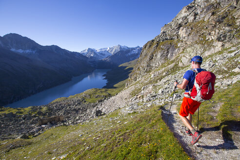 A solo male hiker enjoying the view over Lac des Dix in Val d'H├â┬®r├â┬®mence, in the Swiss Alps. - AURF04532