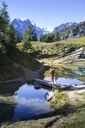 A solo male hiker is walking over a bridge in the Blue Lake above Arolla in the Swiss Alps. - AURF04535