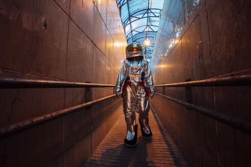Spaceman in the city at night walking in narrow passageway - VPIF00651
