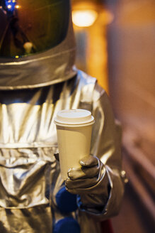 Spaceman in the city at night holding takeaway coffee - VPIF00663