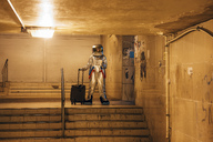 Spaceman in the city at night standing in underpass with rolling suitcase and takeaway coffee - VPIF00666