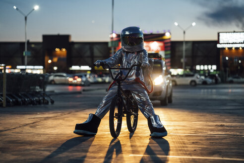 Spaceman in the city at night on parking lot with bmx bike - VPIF00669