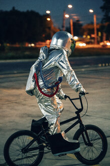 Spaceman in the city at night on parking lot riding bmx bike - VPIF00675