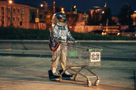 Spaceman in the city at night on parking lot with shopping cart - VPIF00678
