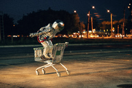 Spaceman in the city at night on parking lot inside shopping cart - VPIF00681