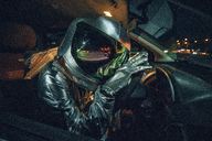 Spaceman sitting in car at night - VPIF00690