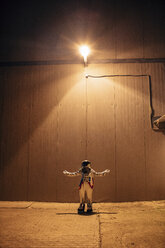 Spaceman standing under lamp at a wall at night - VPIF00693