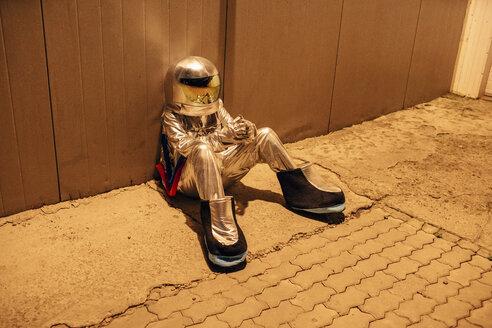 Spaceman sitting at a wall at night - VPIF00696