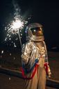 Spaceman standing outdoors at night holding sparkler - VPIF00699