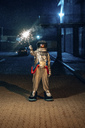 Spaceman standing outdoors at night holding sparkler - VPIF00702