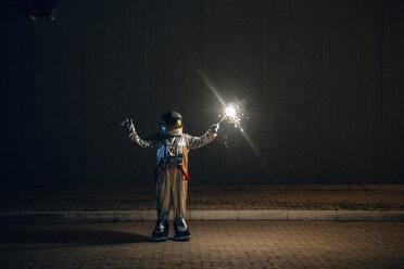 Spaceman standing on a road at night holding sparkler - VPIF00705