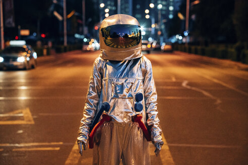 Spaceman standing on a street in the city at night - VPIF00708