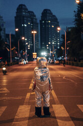 Rear view of spaceman standing on a street in the city at night - VPIF00711