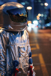 Spaceman standing on a street in the city at night - VPIF00714