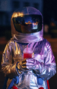Spaceman in the city at night with takeaway drink - VPIF00717