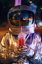 Spaceman in the city at night with takeaway drink - VPIF00720