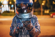 Spaceman on a street in the city at night using smartphone - VPIF00723