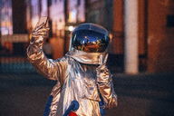 Spaceman in the city at night taking a selfie - VPIF00726