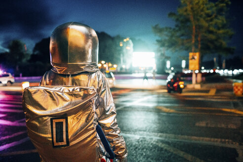 Rear view of spaceman on a street in the city at night attracted by shining projection screen - VPIF00729
