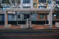 Spaceman sitting on bench at a bus stop at night with soft drink - VPIF00732