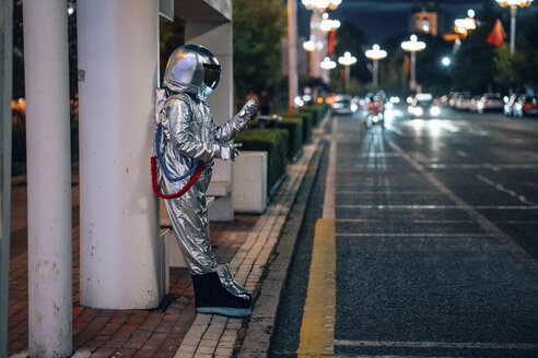 Spaceman standing at a bus stop at night holding cell phone - VPIF00738