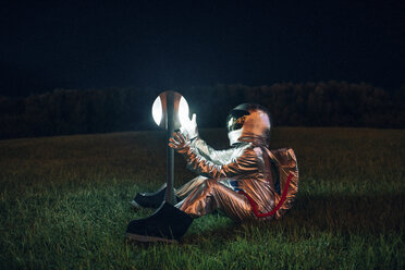 Spaceman sitting on a meadow at night amazed at a lamp - VPIF00741