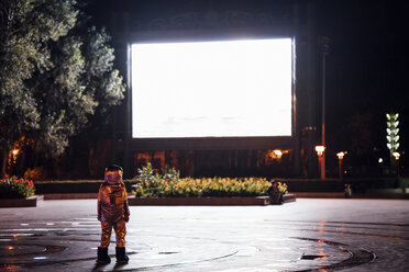 Spaceman on a square at night attracted by shining projection screen - VPIF00753