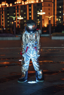 Spaceman standing at a lamp on a city square at night - VPIF00756