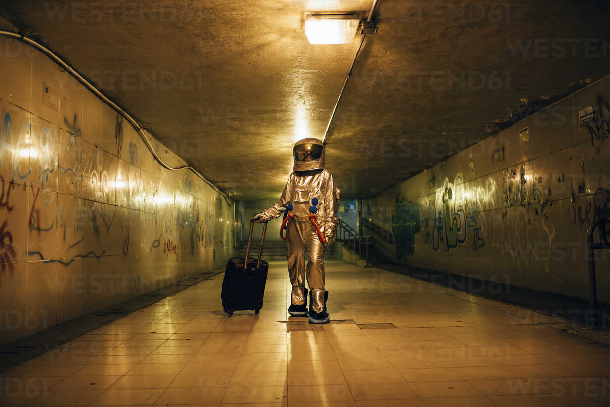 Spaceman in the city at night in underpass with rolling suitcase - VPIF00762 - Vasily Pindyurin/Westend61