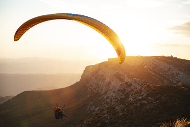 Spain, Silhouette of paraglider soaring high above the mountains at sunset - OCAF00350