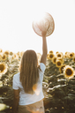 Back view of young woman holding straw hat, standing in a field of sunflowers - OCAF00356