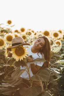 Portrait of a young laughing woman with straw hat, standing in a field of sunflowers - OCAF00362
