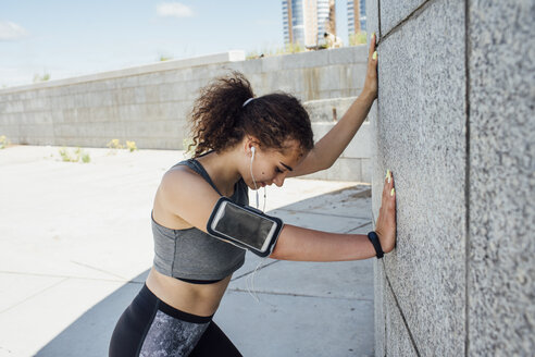 Young athletic woman listening to music leaning against a wall - VPIF00803