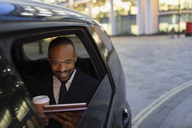 Businessman drinking coffee and using digital tablet in crowdsourced taxi - CAIF22001