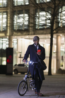 Businessman with bicycle using smart phone on urban sidewalk at night - CAIF22013