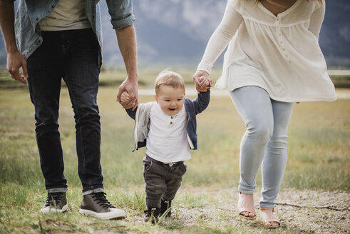 Parents walking with baby son in field - CAIF22025