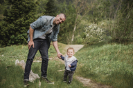 Portrait father and baby son walking on grassy path - CAIF22028